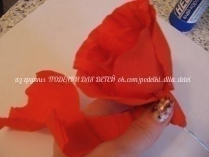 Алая роза из гофрированной бумаги Вам потребуются: лист красной и лист зеленой гофрированной бумаги, проволока для стебля, нитки, клеящий карандаш, ножницыОтрежьте полосу красной гофрированной