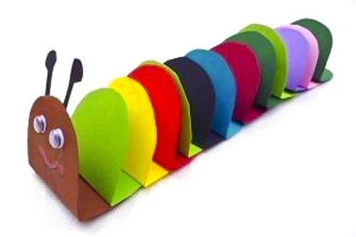 ГУСЕНИЦА ИЗ ЦВЕТНОГО КАРТОНА Понадобится 10-14 овалов, вырезанных из разноцветной бумаги. Сделайте на каждом овале сгиб . Теперь каждый овал горизонтальной стороной приклеивайте к предыдущему