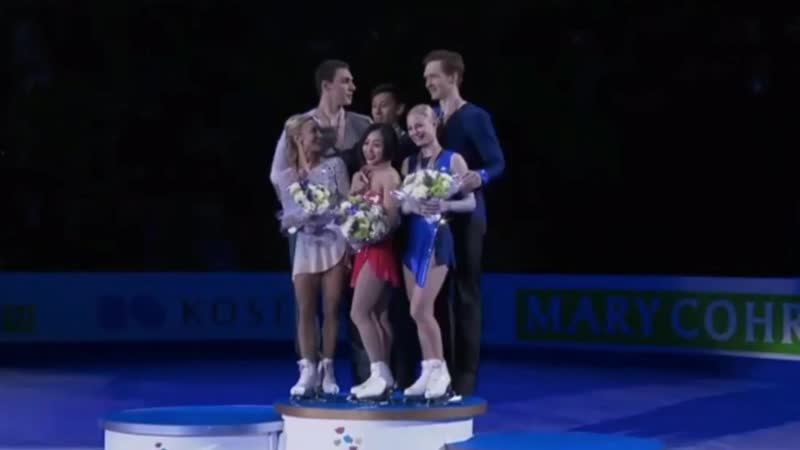 2nd 3rd place winners of World Figure Skating Championships help to lift the champion for podium photo