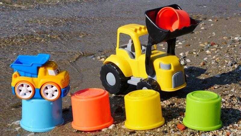 Spielzeug Video für Kinder. Die Spielzeugautos bauen am Strand einen Turm.